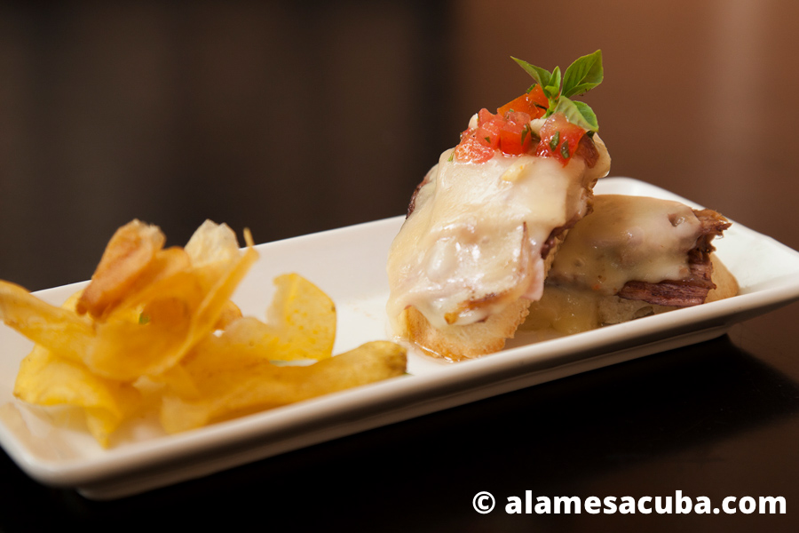 Petit sándwich cubano con los ingredientes clásicos, cerdo asado, jamón pierna y queso gouda acompañado de un crujiente de boniato con albahaca.