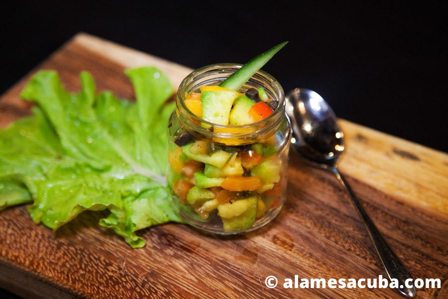 Ensalada de frutas y vegetales. Contiene mango, aguacate, aceitunas negras y pimientos, decorado con pepinos. Todo muy fresco, nutritivo y saludable.