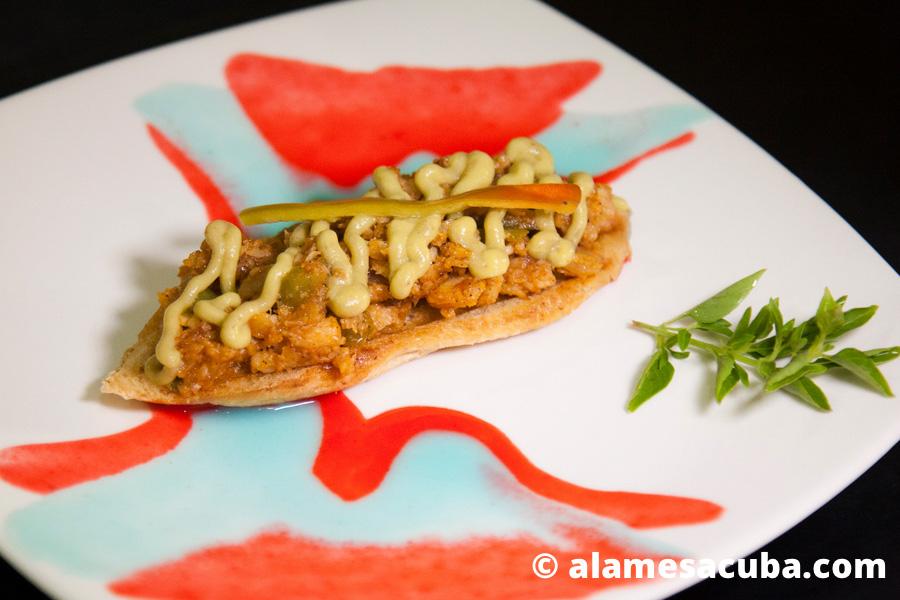 Bruschetta con enchilado de pescado cubierto con un espejo de salsa guacamole decorado con un guinda de pimiento encurtido.