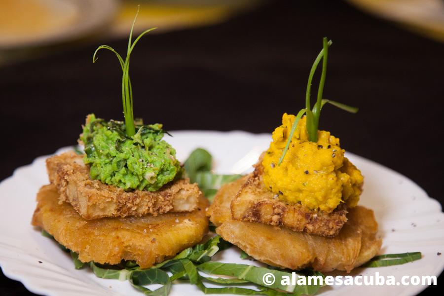 Dos tostones con berenjena empanada, uno acompañado de crema de calabaza y zanahorias y otro con crema de chícharo verde.