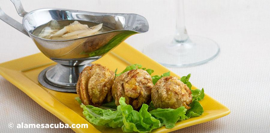 Marranitas - Tostones rellenos con chicharrón sobre una hoja de lechuga fresca y mojo criollo para bañarlos.