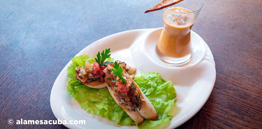 Tapa Mes Amis: Brusqueta marinera con cebolla caramelizada y reducción de vino blanco. Chupito de salmorejo con jamón serrano y queso parmesano con una foccacia.