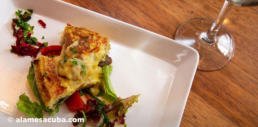 Tapa pazillo: Tortilla española rellena con queso y espinaca sobre una base de ensalada y pétalos de rosas, aromatizado con aceite de oliva.